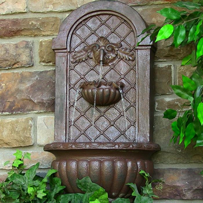 habiller un mur extérieur avec une petite fontaine en style classique en pierre marron, détail sur un mur en grandes pierres rectangulaires en style rustique en couleurs jaunes et marrons