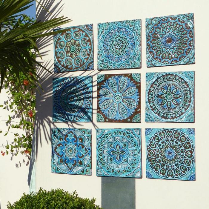 mosaïque en bleu et noir inséré dans un mur en couleur blanc crème extérieur, décorer un mur extérieur de jardin avec des motifs mandales, neuf mandales en mosaïque