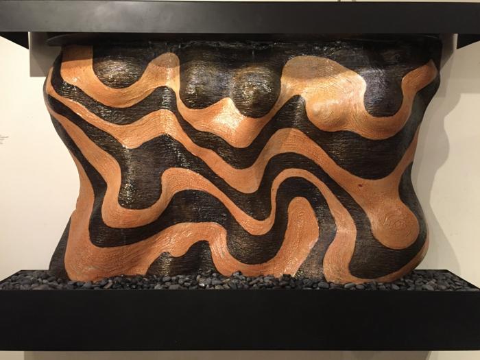 idee deco jardin exterieur, aménagement extérieur maison, figures abstraites en relief en noir et orange, avec la base en pierres noires, bustes de femmes délicatement mis en vue