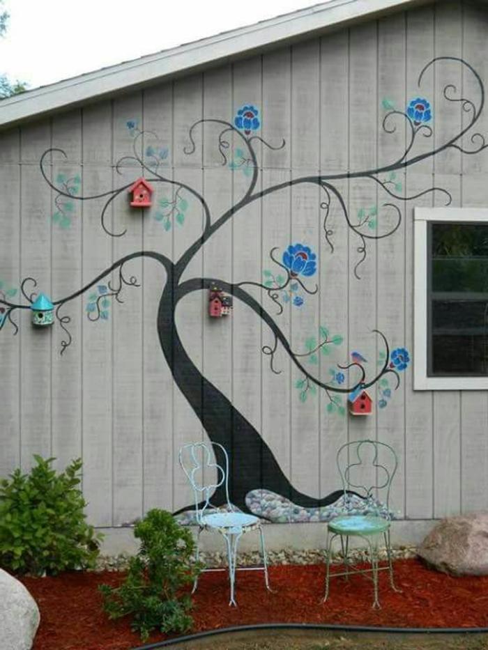 revetement mural exterieur, avec dessin d'arbre noir aux branches ramifiées avec des maisons d'oiseaux aux bouts des branches, quatre maisons d'oiseaux en bois coloré en rouge et bleu pastel