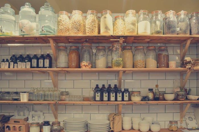 exemple de cuisine style campagne chic avec des étagères en bois ouvertes chargées de plusieurs pots et vaisselle