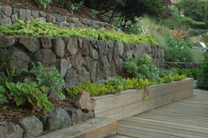 mur en grandes pierres brutes marron et grises, mur vegetal exterieur en vert et jaune, partie en bois clair qui cache la terre et terrain en bois, véranda