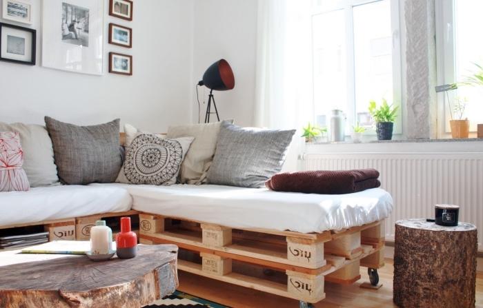 ambiance comfy dans un salon aux murs blancs et au parquet de bois clair aménagé avec canapé d'angle en palettes