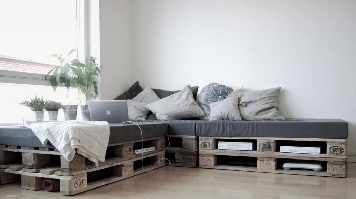 déco de salon minimaliste avec parquet de bois laqué clair et modèle de canapé d'angle en palette diy couvert de coussins