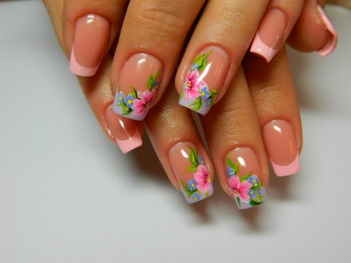 modèle de nail art de style français avec vernis rose pastel sur les bouts des ongles et déco florale en dessin rose vert et bleu