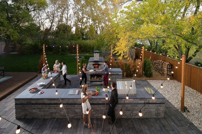 décoration extérieure et ustensile de cuisine aménagée en L avec barbecue et grille en pierre, éclairage extérieur avec guirlande lumineuse
