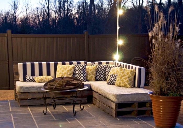 modèle de canapé palette pour coin extérieur au sol en carrelage gris et éclairage extérieur, meuble DIY d'angle
