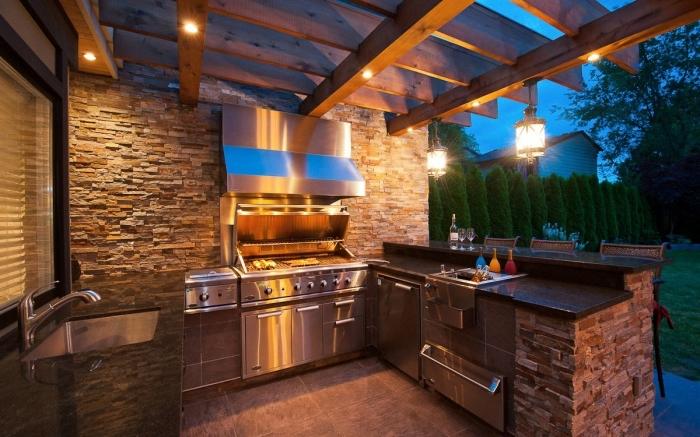 idée pour abri cuisine extérieure avec toit en bois et éclairage led, cuisine d'été avec murs en pierre aménagée en U