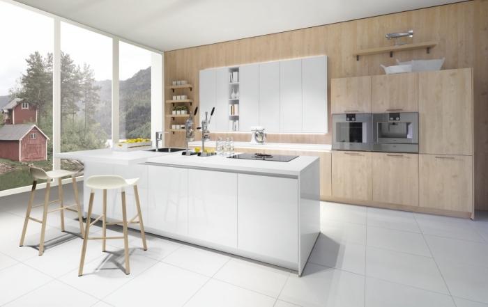 design intérieur moderne dans une cuisine au plafond et sol en carrelage blanc avec meubles de bois clair et ilot central