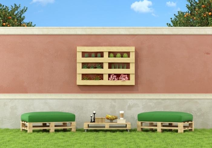 exemple de meubles de jardin en palettes avec deux tabourets à siège vert et une table basse placés sur un gazon vert