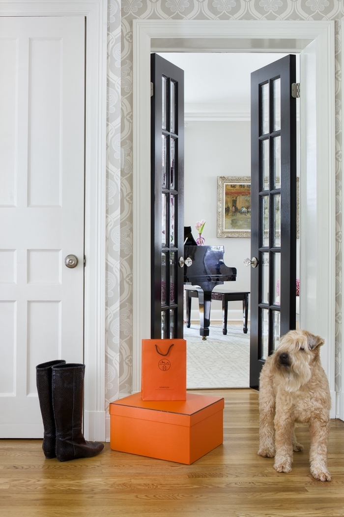 porte interieur vitrée peinte en noir avec encadrement blanc qui constitue un élément déco élégante et chic tout en jouant sur le contraste avec le papier peint à motifs discrets et l'intérieur blanc du salon