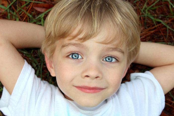 coupe de cheveux pour garçon simple avec une frange longue, cheveux couleur blonde fines, tee shirt blanc