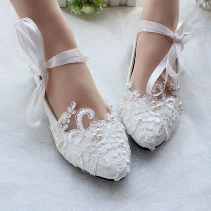 escarpin mariage en dentelle blanche, chaussure de mariée confortable, bouts pointus, surface parsemée de perles blanches de taille diverse, lacets en soie blanche noués autour des chevilles avec des gros nœuds