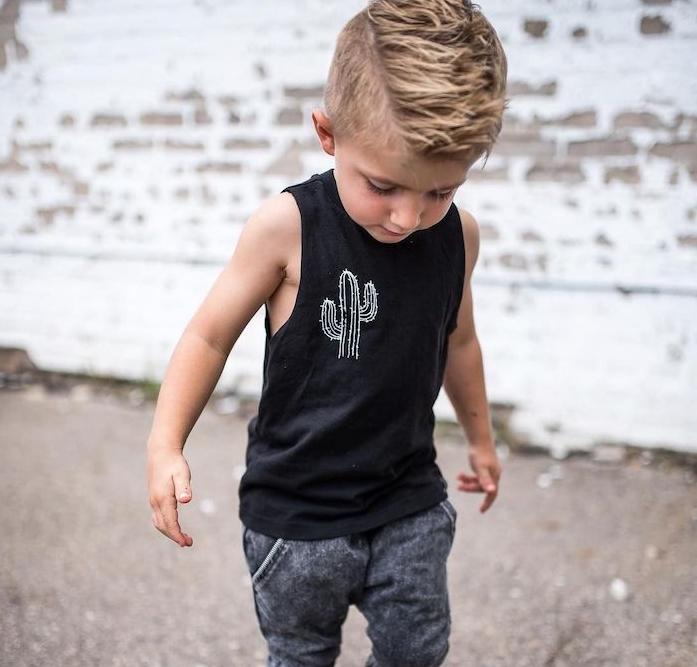 coiffure petit garçon moderne, cheveux de dessus hérissés, undercut avec des cotés rasés, débardeur noir, motif cactus et jean gris et blanc