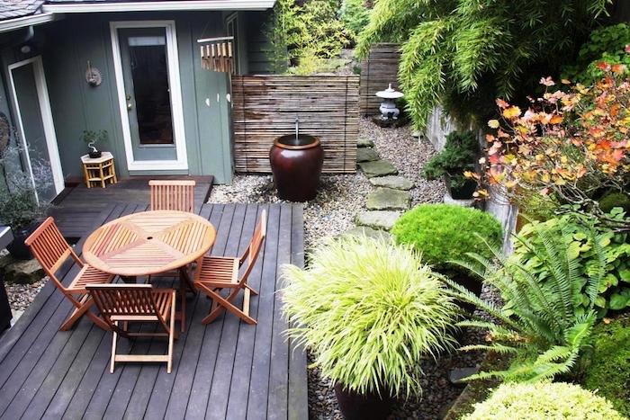 amenager une terrasse en bois avec chaises et table bois, jardin japonais recouvert de gravier, cloture bambou et plantes vertes