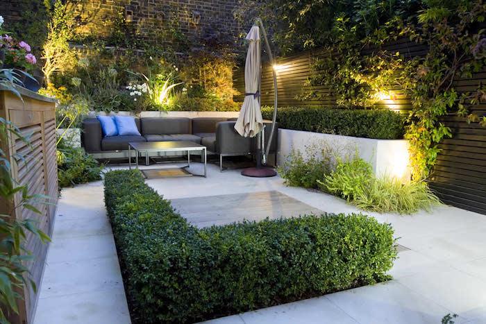 aménagement de jardin avec salon de jardin moderne en canapé gris et table basse bois et metal, mur de bois et mur de briques, bordure de buis, plantes grimpantes
