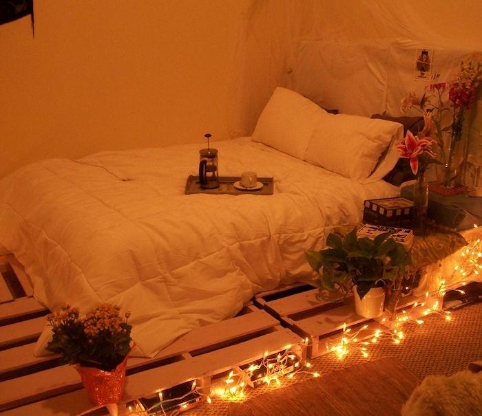lit diy avec palettes sur le sol pour sommier bas style asiatique avec cotés pour table de chevet avec plantes