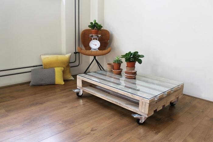 une table basse en palette sur roulettes avec un plateau en verre qui trouvera aussi bien sa place dans un salon vintage ou d'ambiance vintage