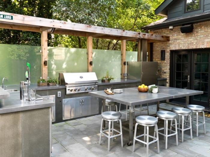 modèle de cuisine ouverte dans le jardin avec équipement et ilot en inox, table à manger rectangulaire avec tabourets