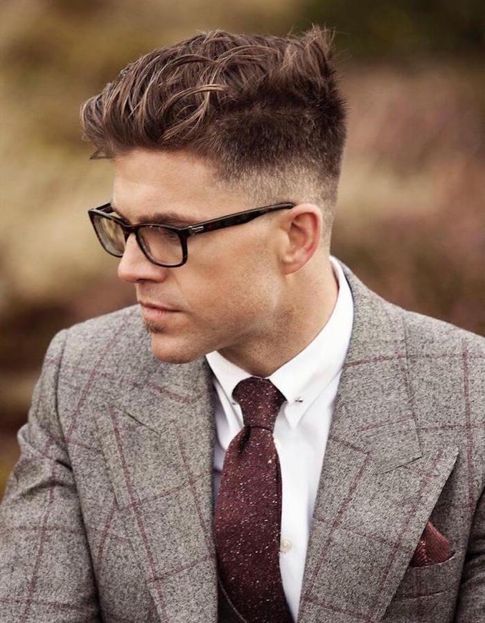 coupe homme dégradé progressif bas sur les cotés et meches sur le dessus avec costume à carreaux gris et lunettes