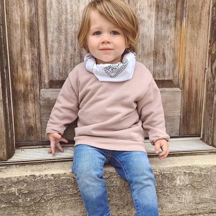petit garçon aux cheveux mi longs avec volume, frange asymétrique, top marron clair, jean bleu, écharpe blanc,