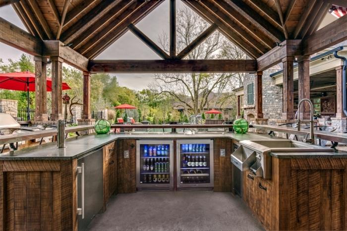 cuisine d'extérieur couverte avec toit de bois solide et équipement en inox, modèle de déco cuisine en U en bois et acier