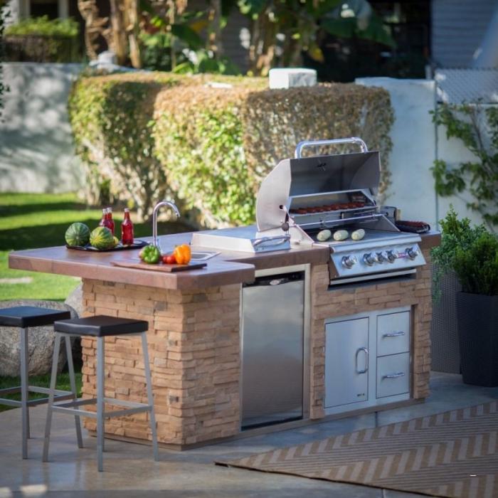 exemple petite cuisine de jardin avec ilot en pierre et équipement en acier inoxydables, petites armoires avec portes en inox