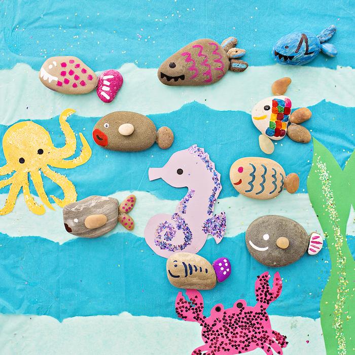 exemple d activité manuelle maternelle avec des galets décorés et transformés en poissons et autres créatures, crabe, pieuvre en papier sur un fond bleu marin