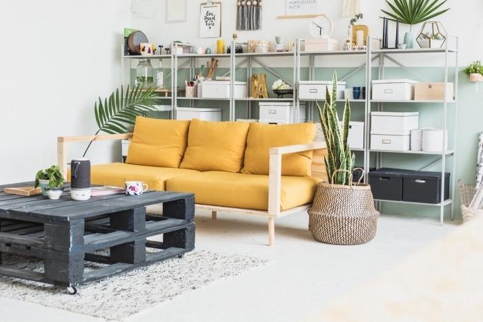ancien garage transformé en loft bohème aménagé avec des meubles diy, une table basse originale avec deux palettes superposées en contraste avec le canapé diy en planches de bois