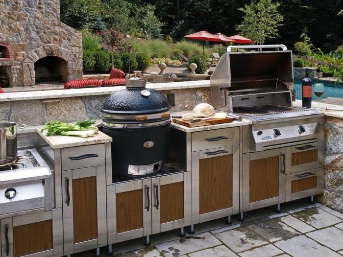 modele de cuisine aménagée au bord de la piscine avec clôture en pierre et équipement en bois solide et inox