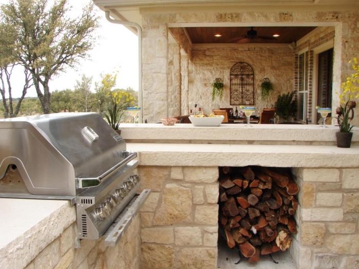 idée comment aménager une cuisine de jardin couverte avec ilot de pierre et équipement barbecue en acier inox