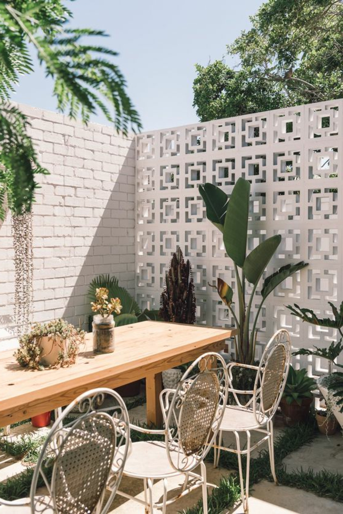 deco mur exterieur, grande table rectangulaire en bois clair, chaises en style rétro en métal blanc, clôture moitié en briques blanches, moitié en métal blanc aux motifs carrés