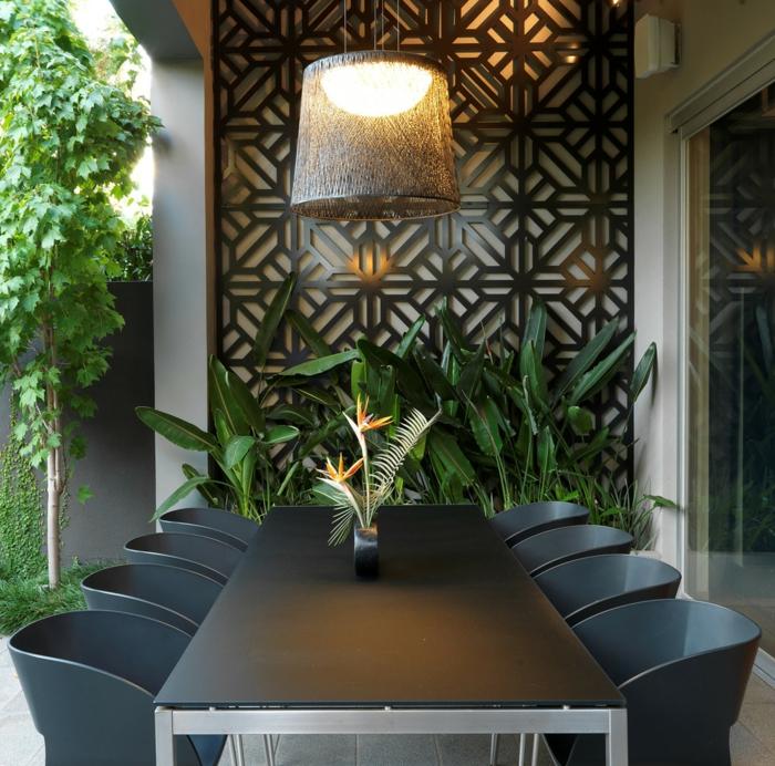 décoration murale extérieure avec un panneau en métal noir aux motifs fleurs stylées, grande table rectangulaire en plan noir avec des pieds en métal clair, huit chaises avec des dossiers en PVC noir, habiller un mur extérieur