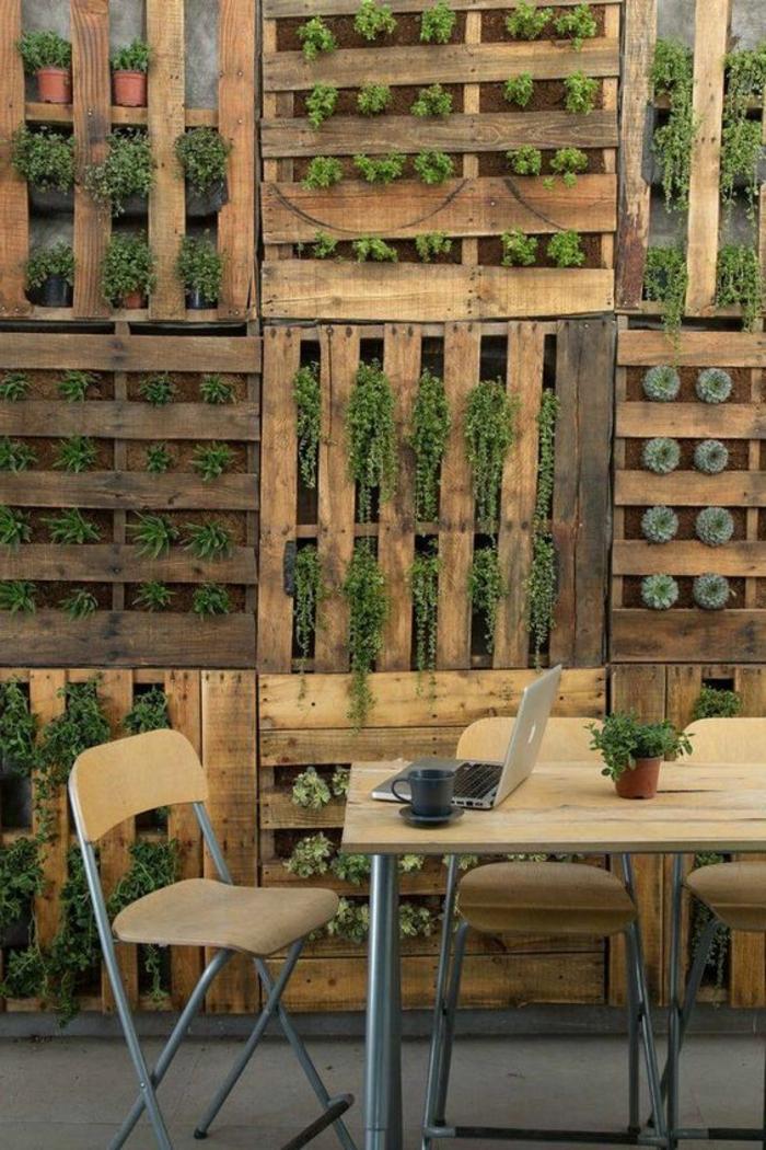 deco mur exterieur en bois de palettes marron avec végétation qui sort par les trous des palettes, mur végétal pour terrasse ou jardin, grande table carrée avec plan en bois clair, trois chaises pliantes en bois PVC et pieds en tubes en aluminium