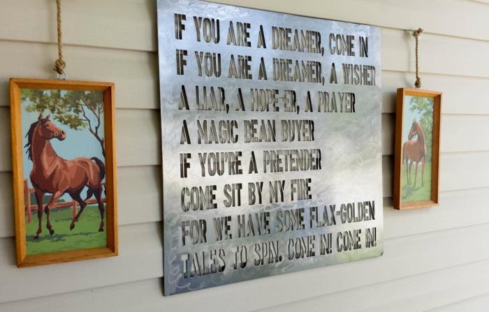 décoration murale extérieure, aménagement extérieur maison, mur revêtu de métal couleur ivoire, panneau en métal ciselé avec des messages d'encouragement, deux tableaux avec des chevaux en plein air