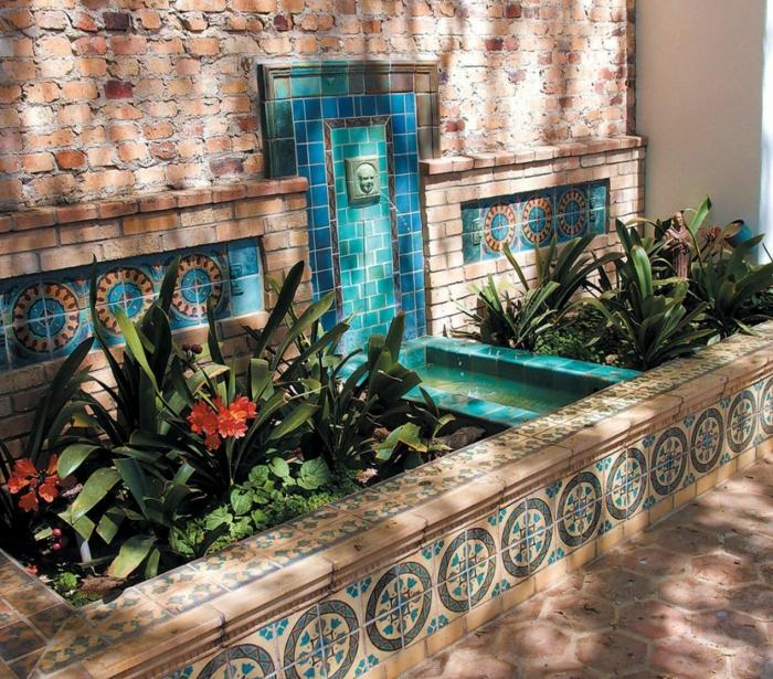 revetement mural exterieur, fontaine de jardin avec tete d'homme et de l'eau qui sort de sa bouche, mosaïque en bleu turquoise et vert lac, mur en biruqes rouges