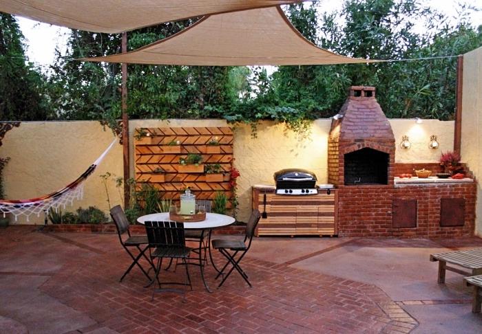déco de jardin avec hamac suspendu et coin de petite cuisine équipée de barbecue grille en briques rouges