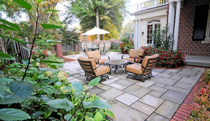 coin salle à manger en table et chaises et coin repos en table et chaise metalliques, dalles béton, bordure fleurie, maison traditionnelle