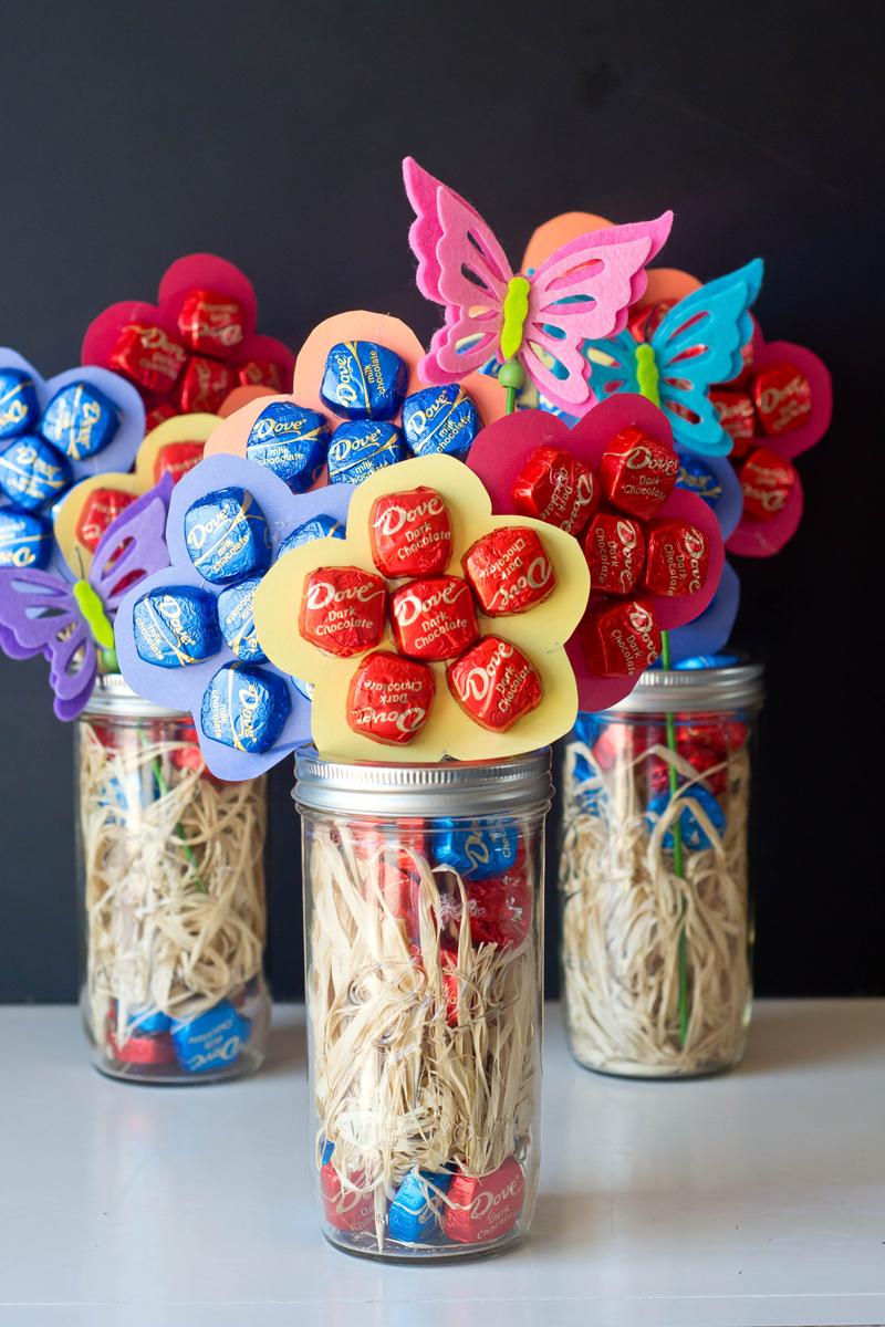 comment faire un bouquet de bonbons collés sur une fleur en papier, bonbons enveloppes rouges et bleues dans un pot en verre et papillons coloré