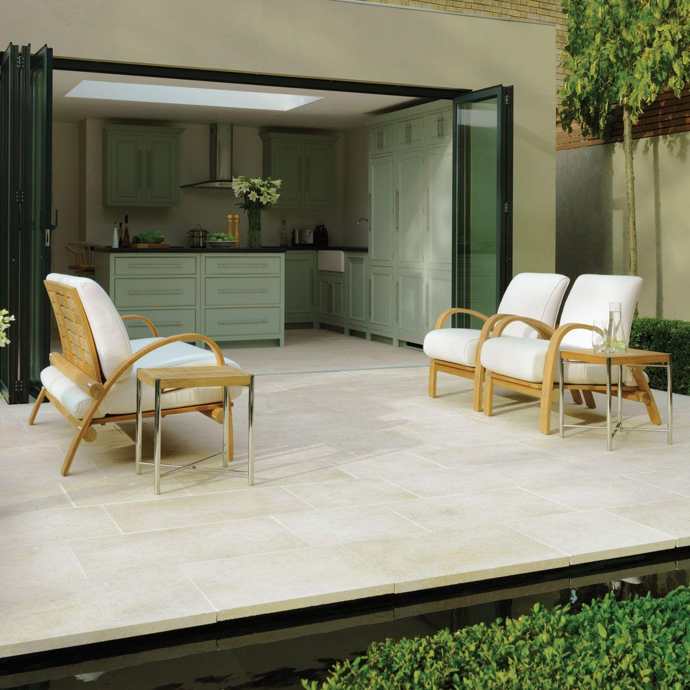 exemple de cuisine vert menthe qui s ouvre sur une terrasse exterieure recouverte de dalles, chaises bois, coussins d assise blancs