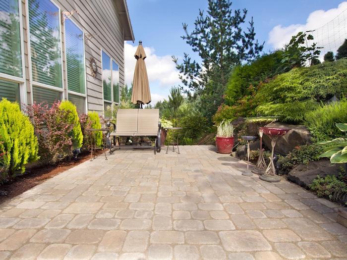 comment cloture une terrasse maison exterieure, rocaille fleurie, constituée de roches et plantes, bordure de petits arbres, revetement pierre, chaise longue double