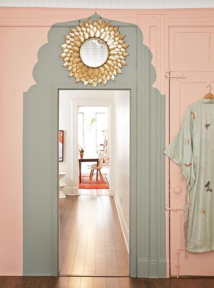 un motif oriental peint en gris autour de l'encadrement de porte en joli contraste avec les murs en rose