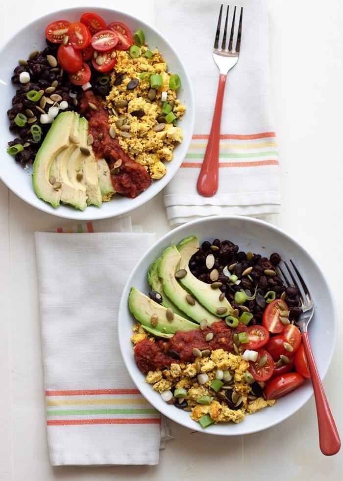 un repas du matin plein de saveur, un bol de petit déjeuner équilibré de tofu brouillé, tranches d'avocat, tomates et haricots noirs