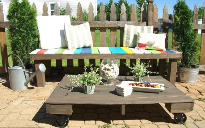 aménager un coin de détente dans le jardin avec un simple banc en bois récup et une table basse exterieur montée sur roulettes, réalisée avec une palette