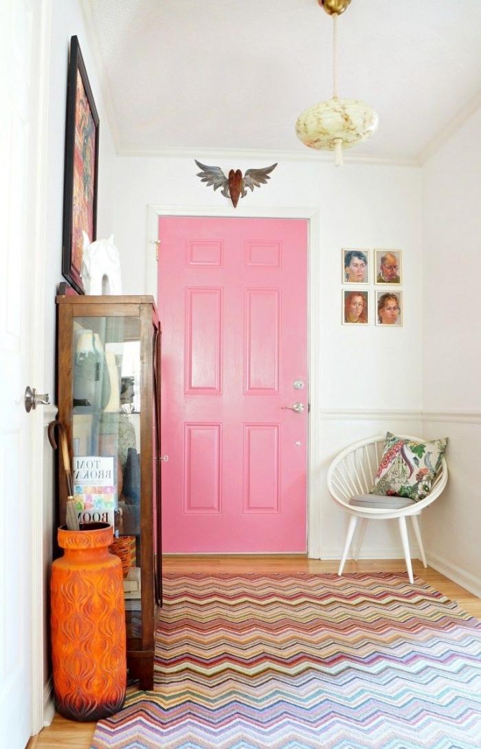 la porte d'intérieur rose bonbon et les motifs colorés sur le tapis et le coussin apporte de la fraîcheur et de la douceur dans cet chambre vintage