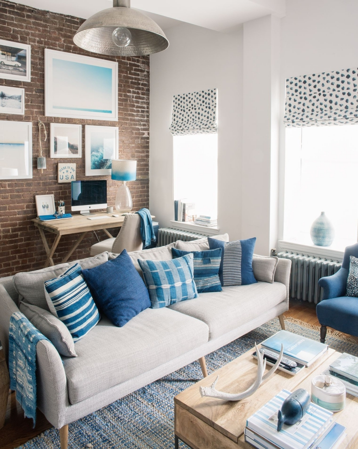 petit studio en tons neutres égayé par des coussins dépareillés en nuances de bleu et une petite déco à inspiration bord de mer