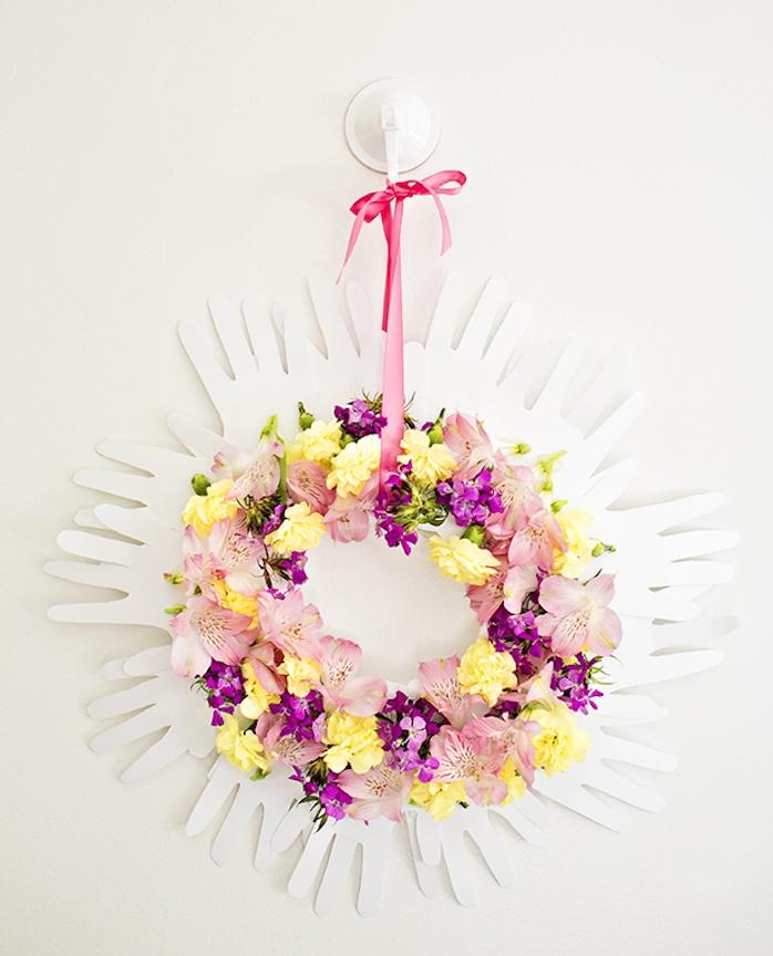 couronne d empreintes de main en papier et fleurs colorés accrochés sur un ruban rose, cadeau maitresse fin d année