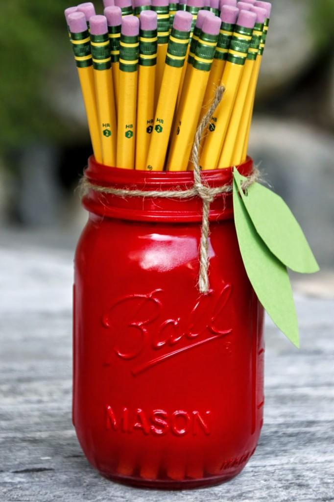 pot à crayon imitation pomme rempli de crayons, bricolage avec pot en verre recyclé et repeint en rouge, feuilles de papier vertes