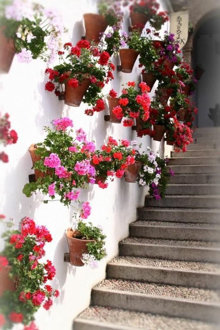 habillage mur exterieur avec des pots de fleurs rouges et roses, idee deco jardin exterieur, décoration murale extérieure, mur blanc, escalier aux marches larges