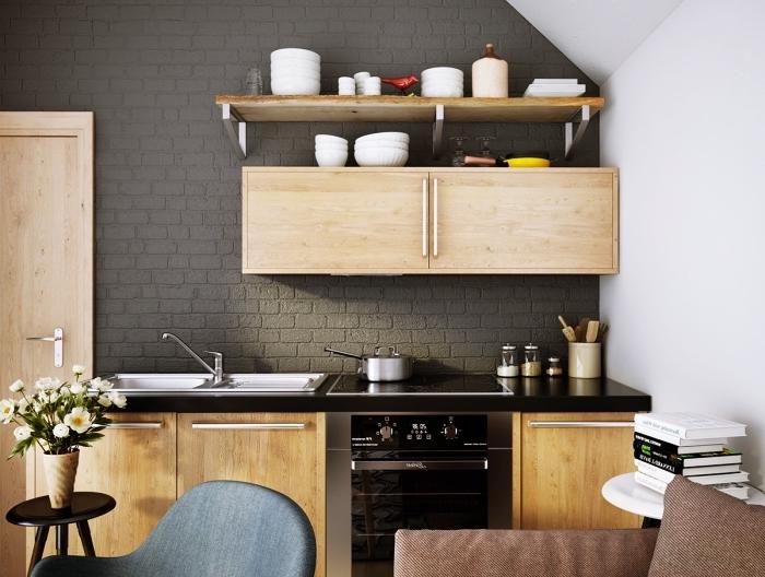 modèle de cuisine tendance aux murs et plafond blancs avec pan de mur en briques gris anthracite et meubles de bois clair